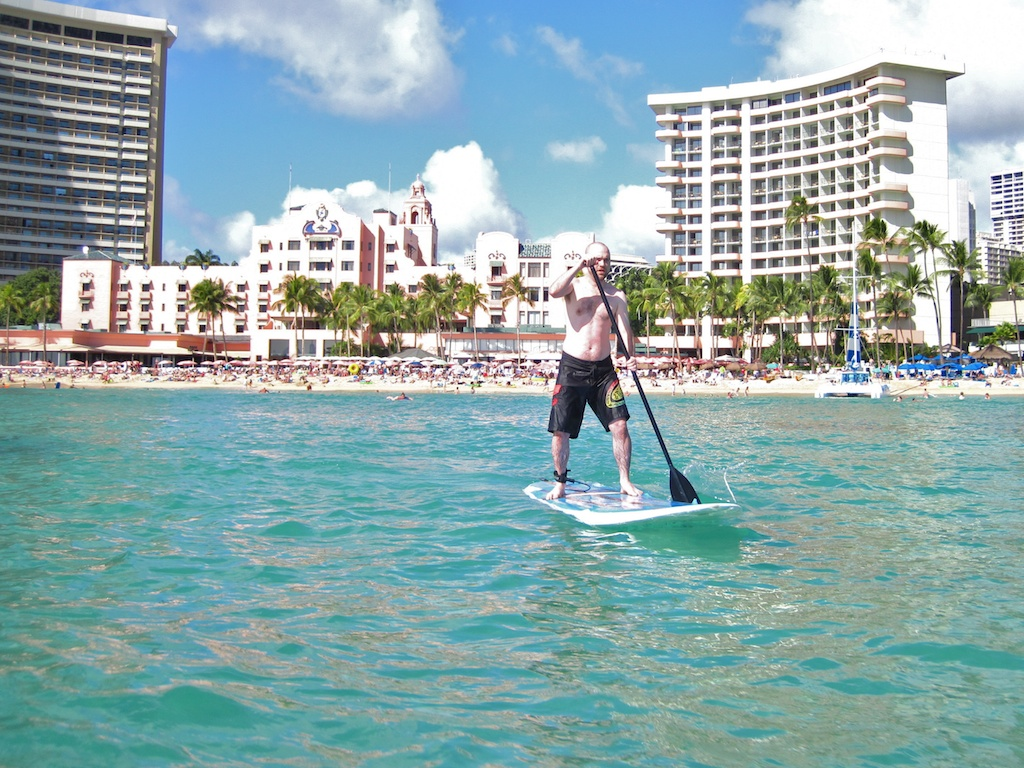 man standing on paddleboard in ocean